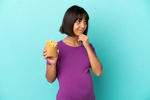 Femme enceinte tenant des chips frites sur fond isolé et levant