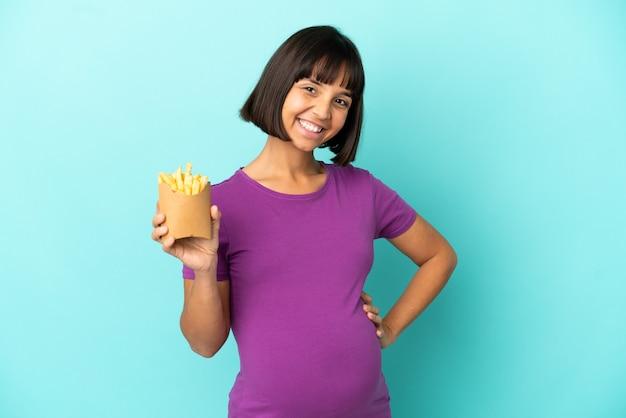 Femme enceinte tenant des chips frites sur fond isolé posant avec les bras à la hanche et souriant