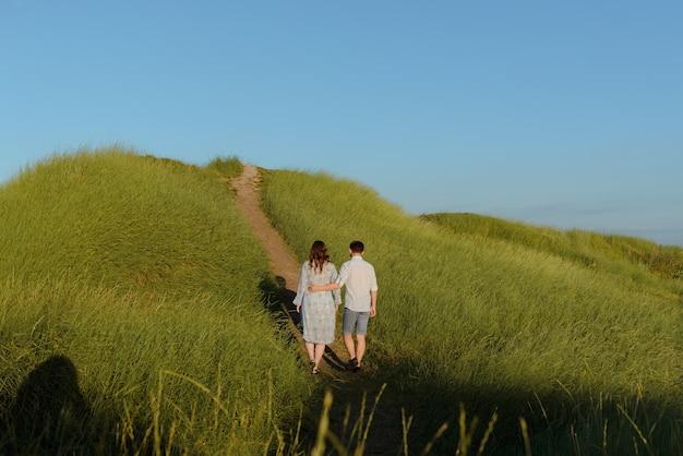 Femme enceinte tenant la main avec son mari lors d'une promenade sur le terrain au coucher du soleil. héhé et nouveau-né.