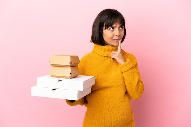 Femme enceinte tenant des pizzas et des hamburgers isolés sur fond rose ayant des doutes en levant les yeux