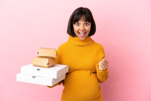 Femme enceinte tenant des pizzas et des hamburgers isolés sur fond rose célébrant une victoire en position de vainqueur