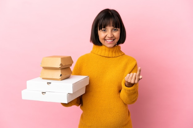 Femme enceinte tenant des pizzas et des hamburgers isolés sur fond rose faisant le geste à venir