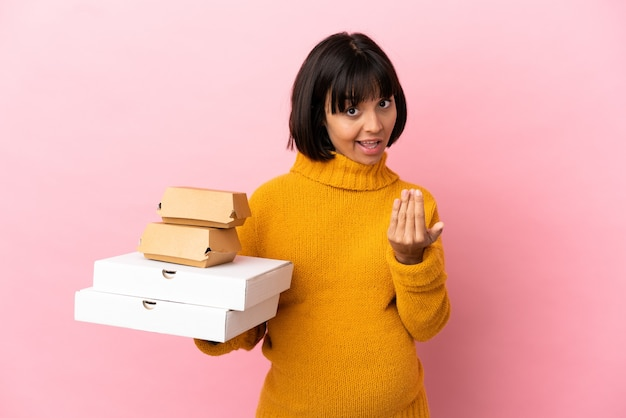 Femme enceinte tenant des pizzas et des hamburgers isolés sur fond rose invitant à venir avec la main. heureux que tu sois venu