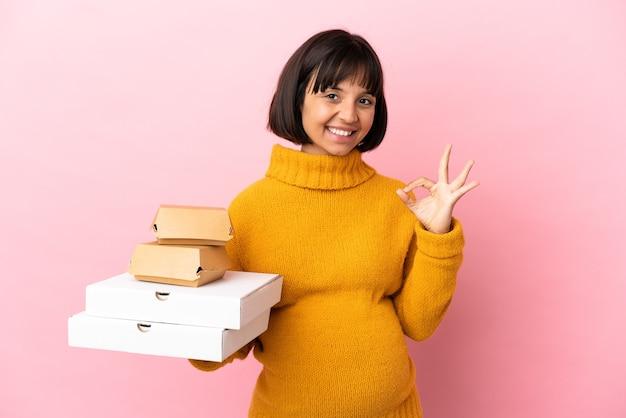 Femme enceinte tenant des pizzas et des hamburgers isolés sur fond rose montrant un signe ok avec les doigts
