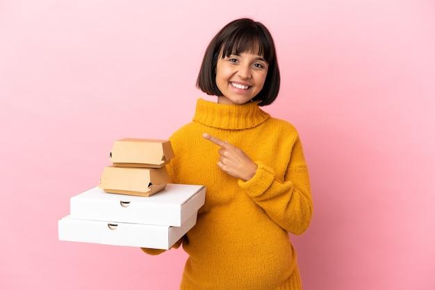 Femme enceinte tenant des pizzas et des hamburgers isolés sur fond rose pointant vers le côté pour présenter un produit