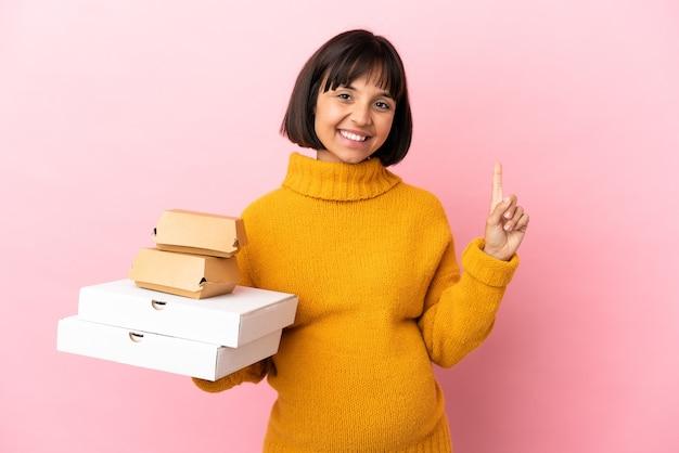 Femme enceinte tenant des pizzas et des hamburgers isolés sur fond rose pointant vers une excellente idée