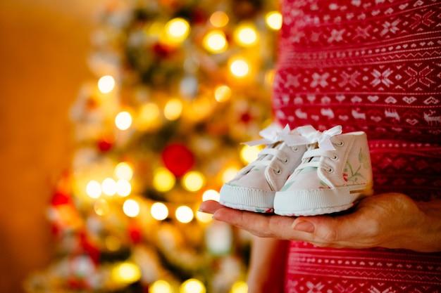 Une femme enceinte tient des chaussures mignonnes pour bébés dans les mains à l'arbre de noël.