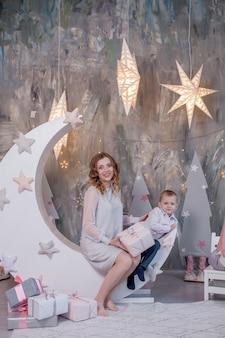Femme enceinte touchant son ventre dans un studio de décoration avec des étoiles lune maternité