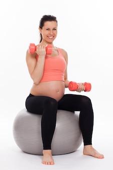 Femme enceinte travaillant avec des haltères