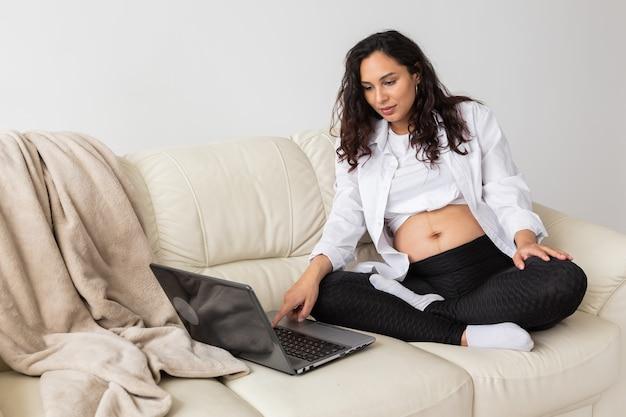Femme enceinte utilisant un ordinateur portable alors qu'elle était assise sur un canapé dans le salon à la maison.