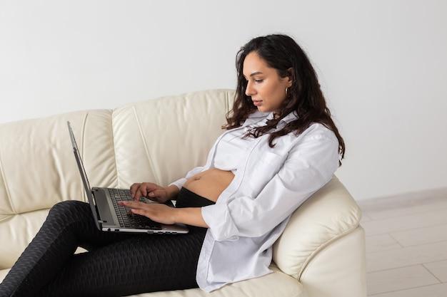 Femme enceinte utilisant un ordinateur portable alors qu'elle était assise sur un canapé dans le salon à la maison