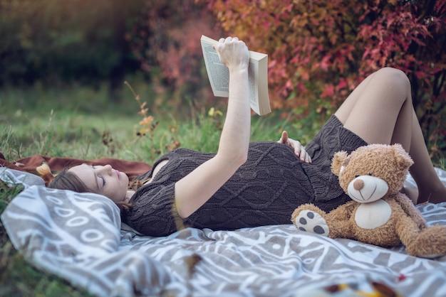 Une femme enceinte avec un ventre se couche sur une couverture et lit des histoires pour le bébé.