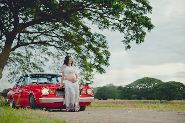 Femme enceinte et voiture rétro garée dans une rue de la vieille ville.