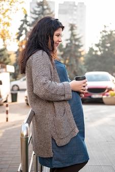 Femme enceinte vue de côté avec une tasse de café en plein air
