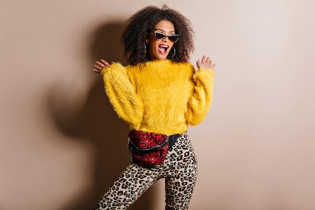 Femme enchanteresse à lunettes de soleil posant avec émotion sur un mur marron