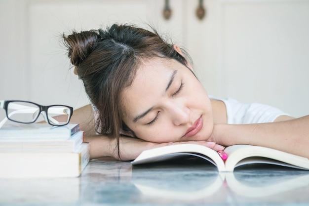 Femme endormie après avoir fatigué de lire avec un livre sur une table en marbre