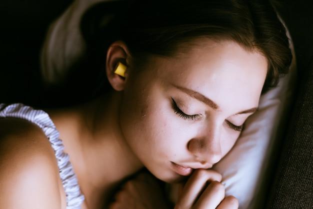 Femme endormie avec des bouchons d'oreilles dans les oreilles