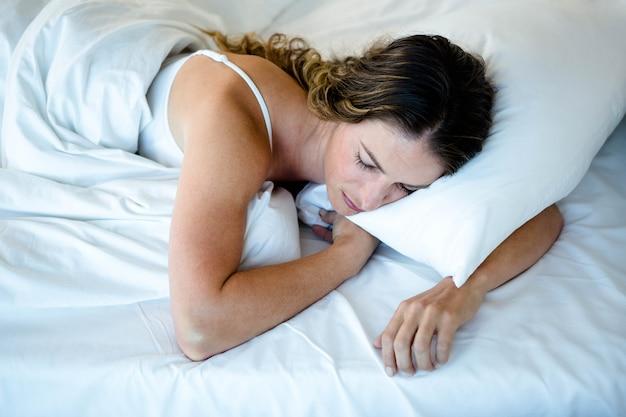 Femme endormie dans son lit, couchée sur le ventre