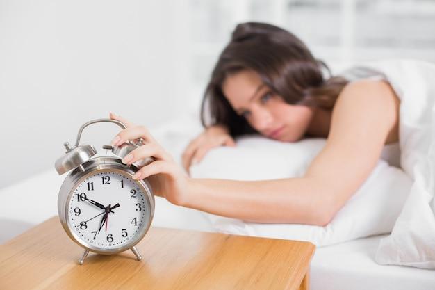 Femme endormie dans son lit, étendant la main au réveil
