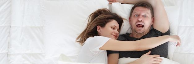 Femme endormie sur l'homme en vue de dessus de lit. notion de relations familiales