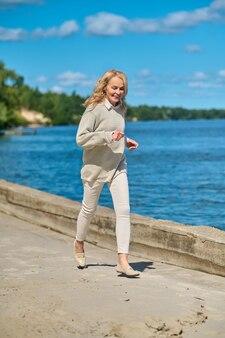 Femme énergique joyeuse jogging près de la mer