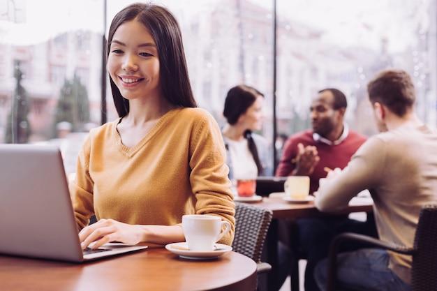 Femme énergique optimiste douce tapant tout en riant et en dégustant un café