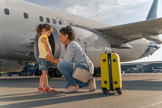 Femme et enfant attendant le vol près d'un avion blanc