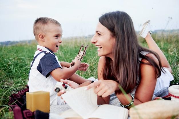 Femme et enfant avec avion dans ses mains passent du bon temps à pique-niquer sur le terrain.