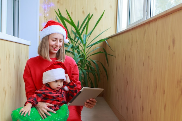 Une femme avec un enfant en chapeaux rouges de santa félicitant la famille ou les amis avec une tablette.