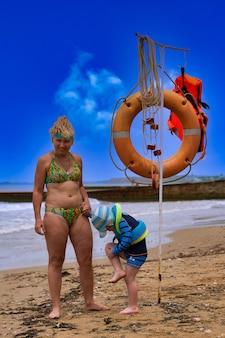 Une femme et un enfant à côté d'un poste de sauvetage en mer