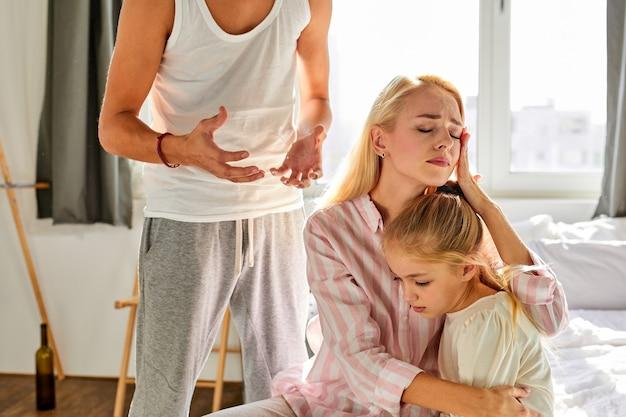 Une femme avec un enfant endure le comportement dégoûtant de son mari dans la maison, la femme est assise avec une enfant fille la protégeant de papa cruel