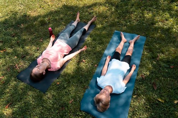 Femme et enfant faisant du yoga plein coup