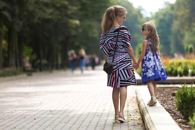 Femme et enfant fille tenant les mains à l'extérieur.