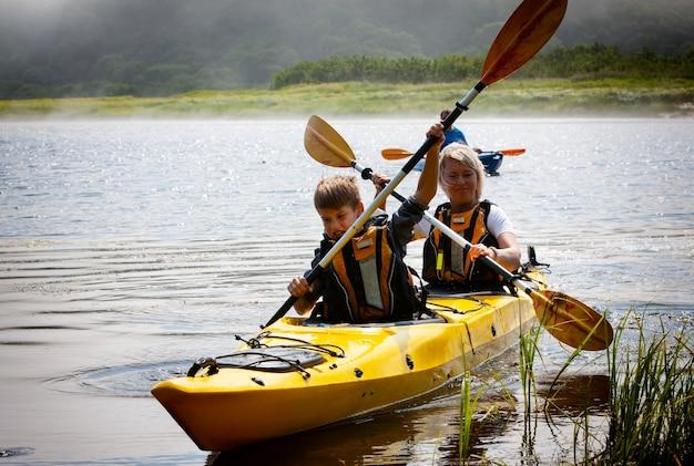 La femme avec un enfant sur le lac et monter en kayak