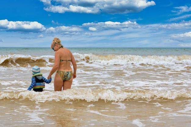 Une femme et un enfant marchent dans la mer en se tenant la main, vue de dos. baignade en famille dans la mer