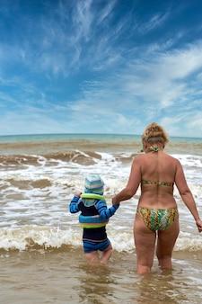 Une femme et un enfant marchent dans la mer se tenant la main, vue de dos