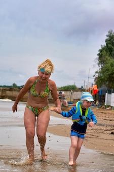 Une femme et un enfant marchent le long de la mer se tenant la main