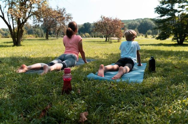 Femme et enfant pleins sur des tapis de yoga