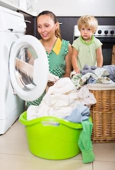 Femme avec enfant près de la machine à laver