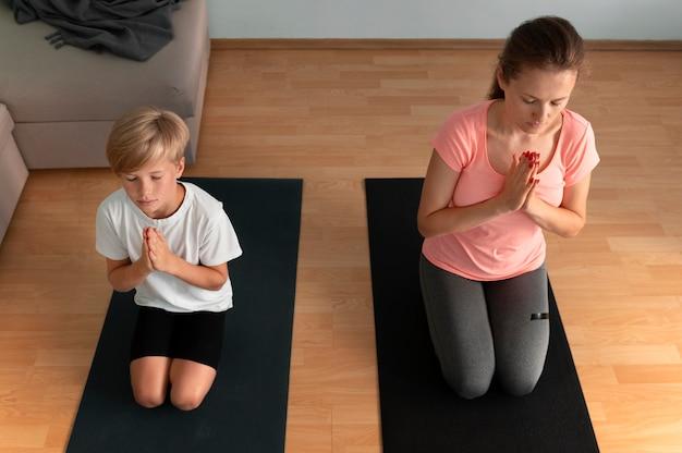 Femme et enfant sur un tapis de yoga plein coup