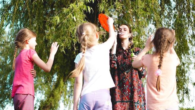 Femme et enfants jouent avec des ballons de savon