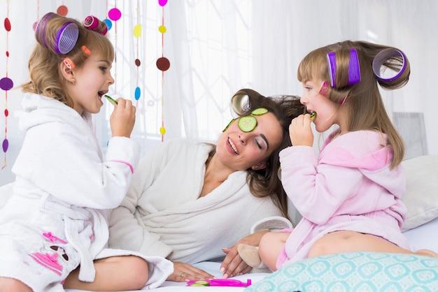 Femme et enfants sur le lit.