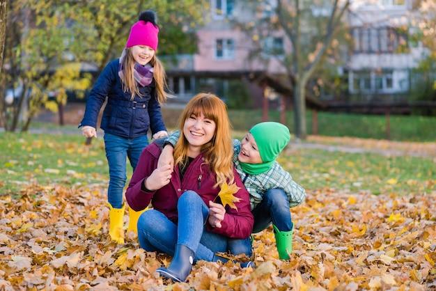 Femme avec des enfants préadolescents au cours de la marche d'automne