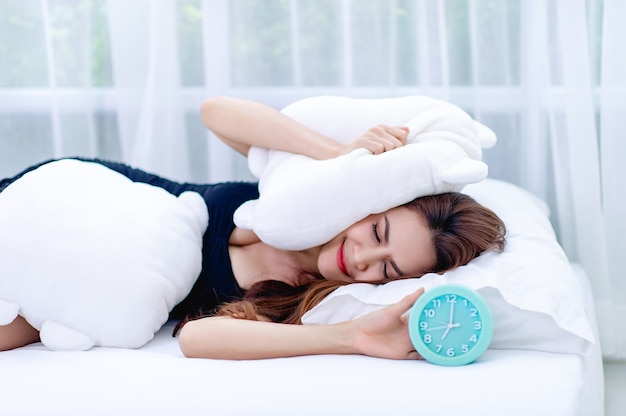 La femme a enlevé l'oreiller de l'oreille pendant que le réveil sonnait le matin. l'idée de se réveiller pour aller travailler à l'heure