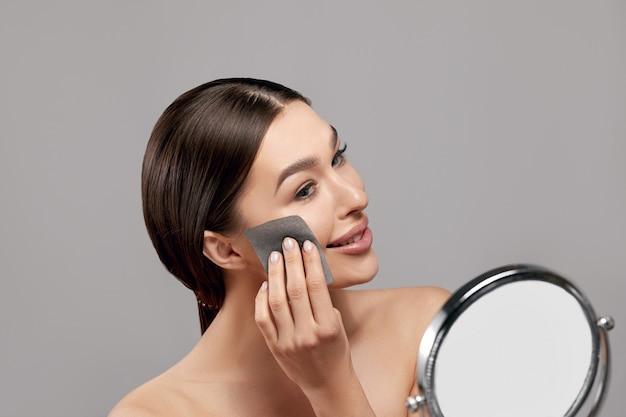 Femme enlever l'huile du visage à l'aide de papiers buvards à la recherche dans le miroir