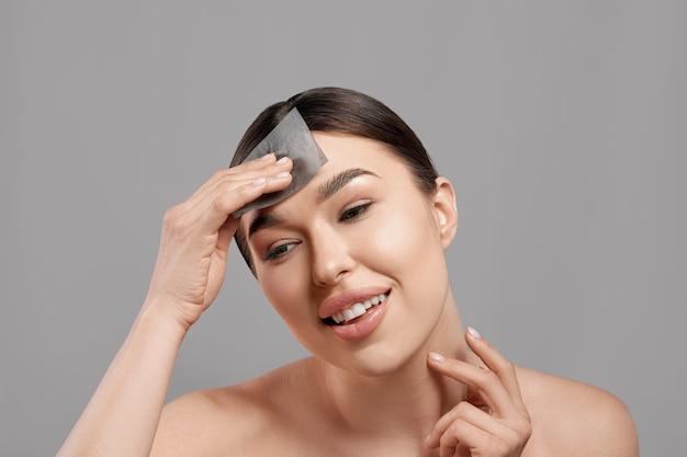 Femme enlever l'huile du visage à l'aide de papiers buvards