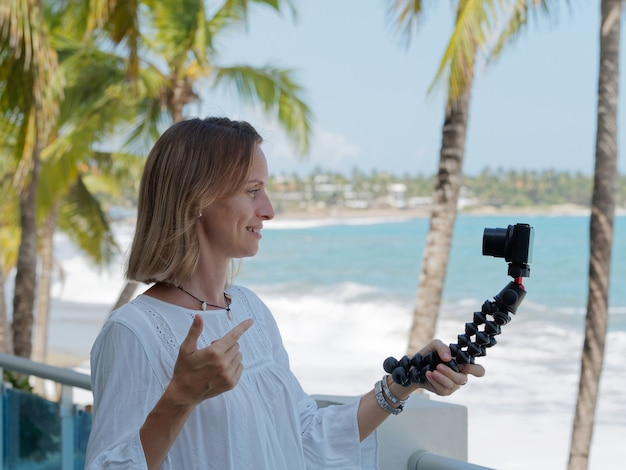 Femme enregistrant un blog de voyage sur la plage. fond d'arbre océan et palmiers.