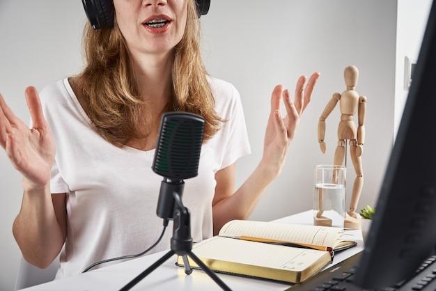 Femme enregistrant un podcast en ligne à la maison, concept de podcasting