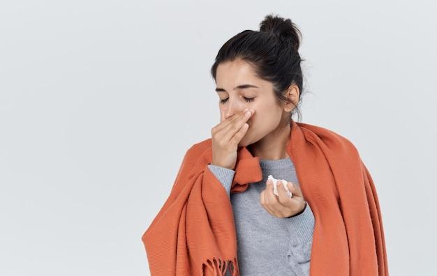 Une femme enrhumée s'essuie le nez avec une grippe mouchoir