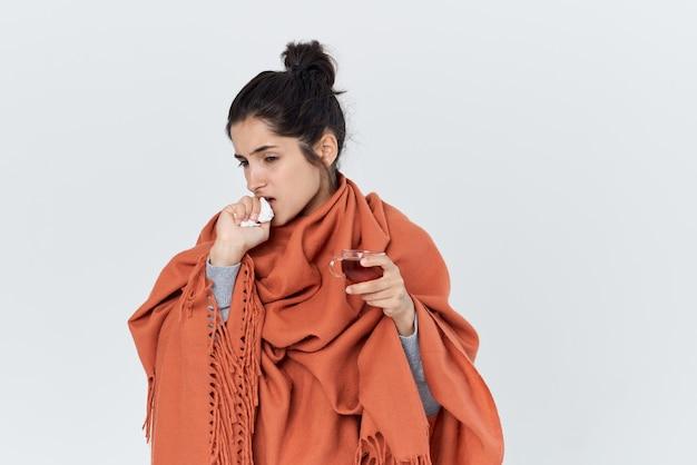 Une femme enrhumée s'est couverte d'un traitement au thé en couverture